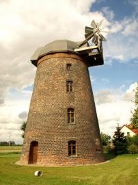 Větrný mlýn holandského typu. Proti větru se samočinně natáčí jen dřevěná střecha s větrným kolem.