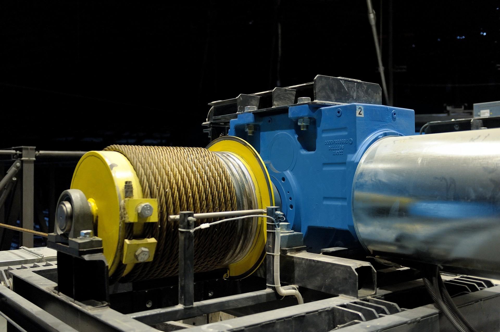 Pohon zvedací plošiny zajišťují čtyři asynchronní motory sklecovou kotvou. Vždy dva pohony na krátké straně plošiny jsou pak mechanicky spojeny pomocí kloubové hřídele.